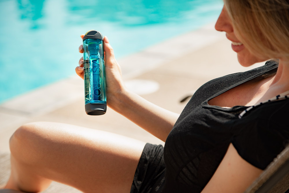 woman using personal cooling mister outdoors