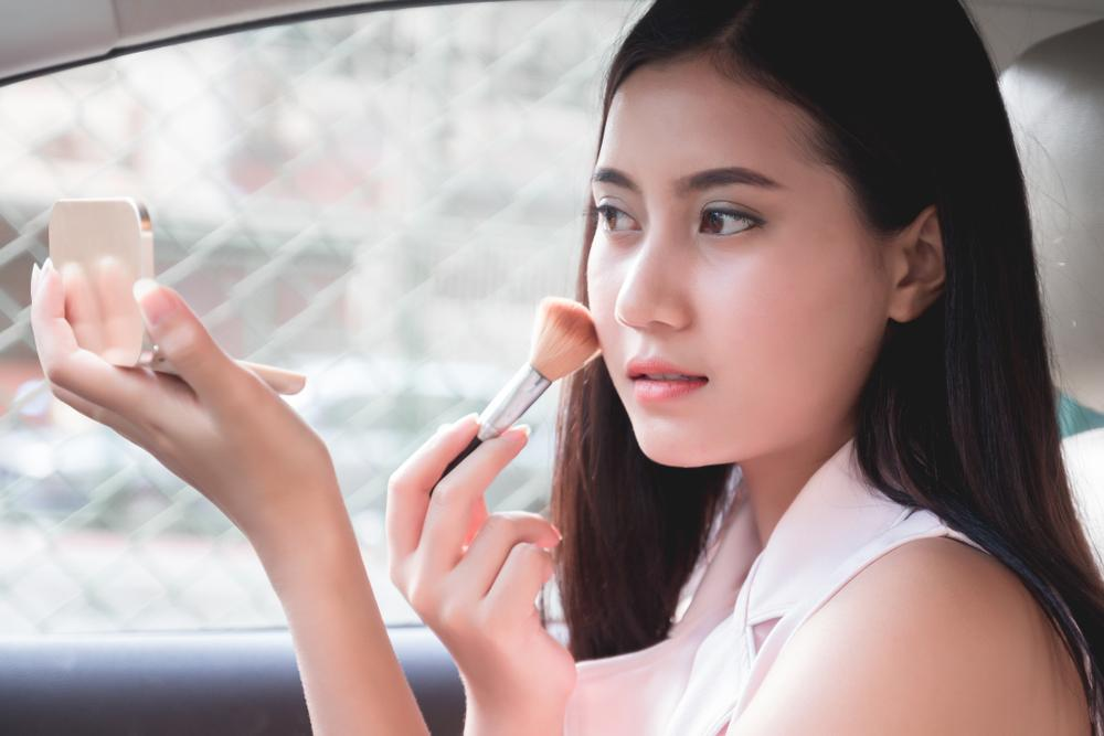 woman applying make up in car skincare