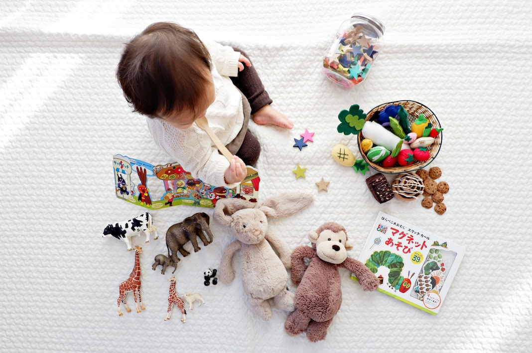 baby playing with toys on bed