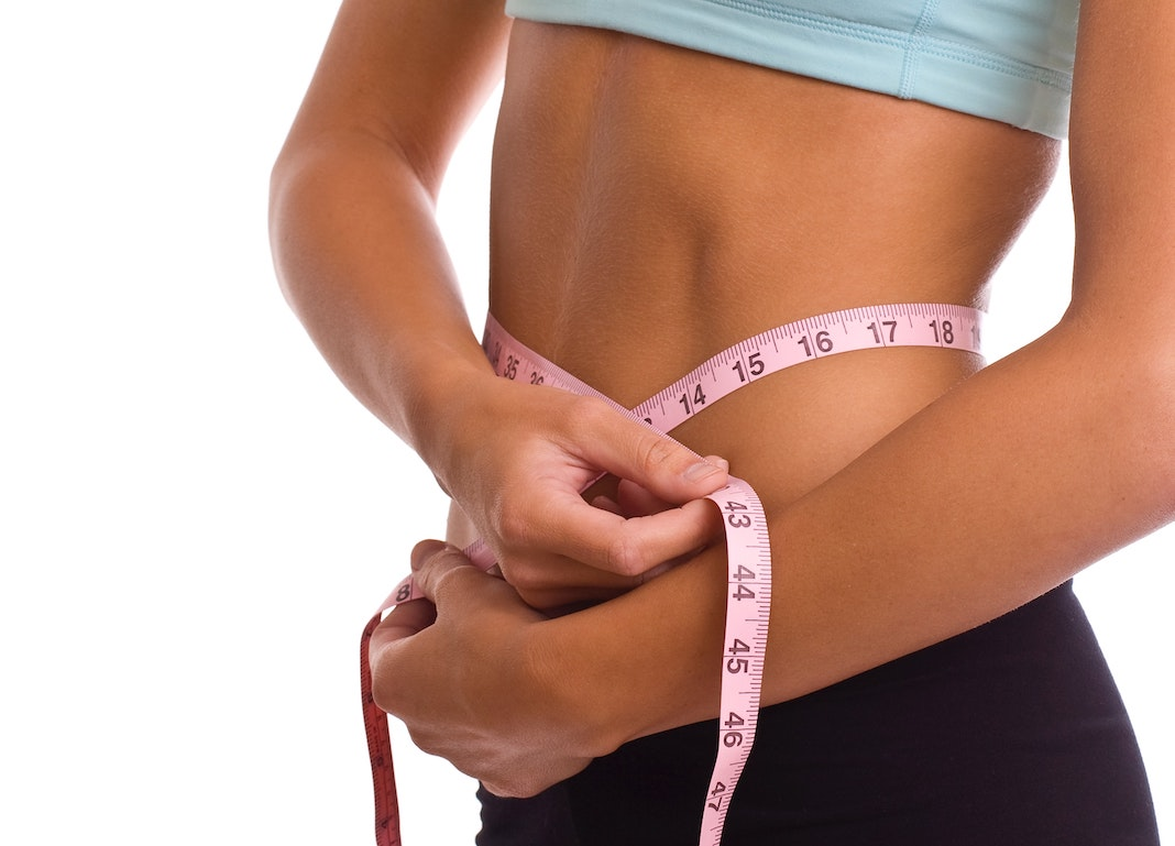 woman using measuring tape to measure waist size
