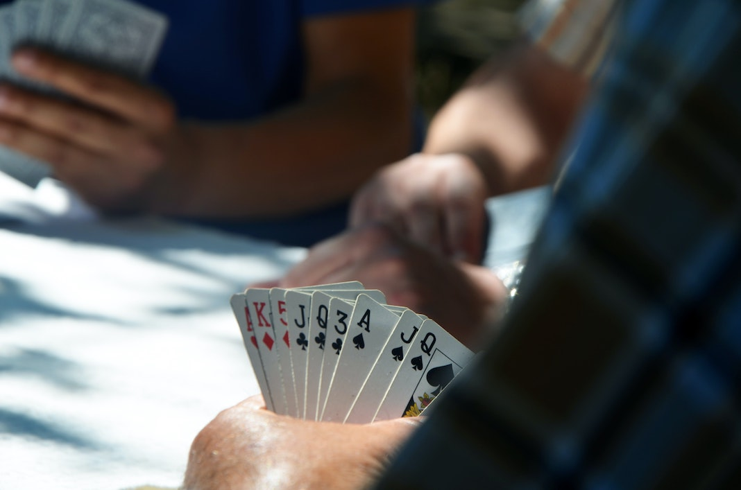 person playing card game at a table in casino