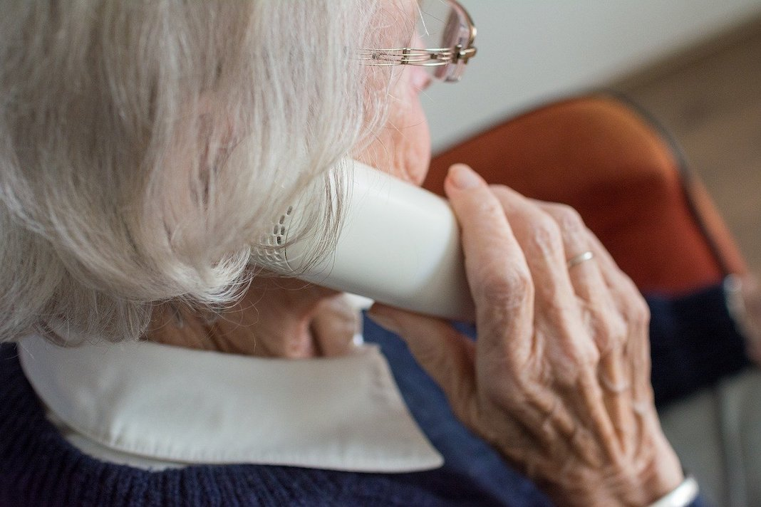 elderly woman talking on the phone with family