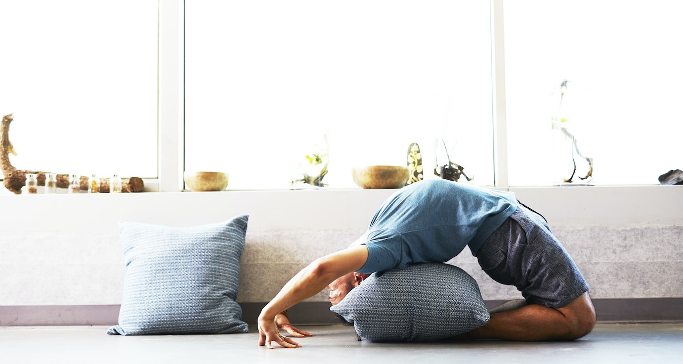 man doing a yoga backbend with pillow supports