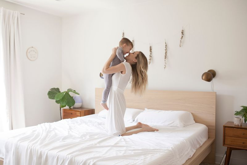 woman and child playing in bed kickee white bedsheets lifestyle