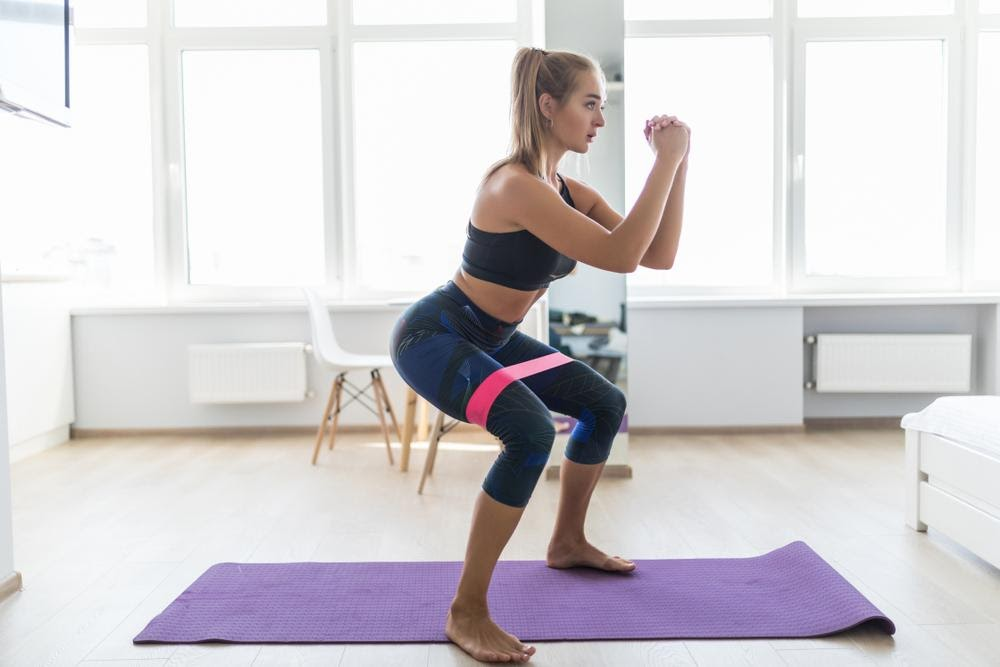 woman working out at home using resistance bands
