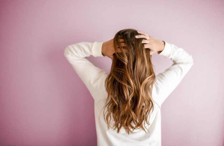 woman scratching her scalp and hair from behind