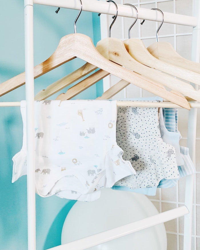 used baby clothes on rack drying